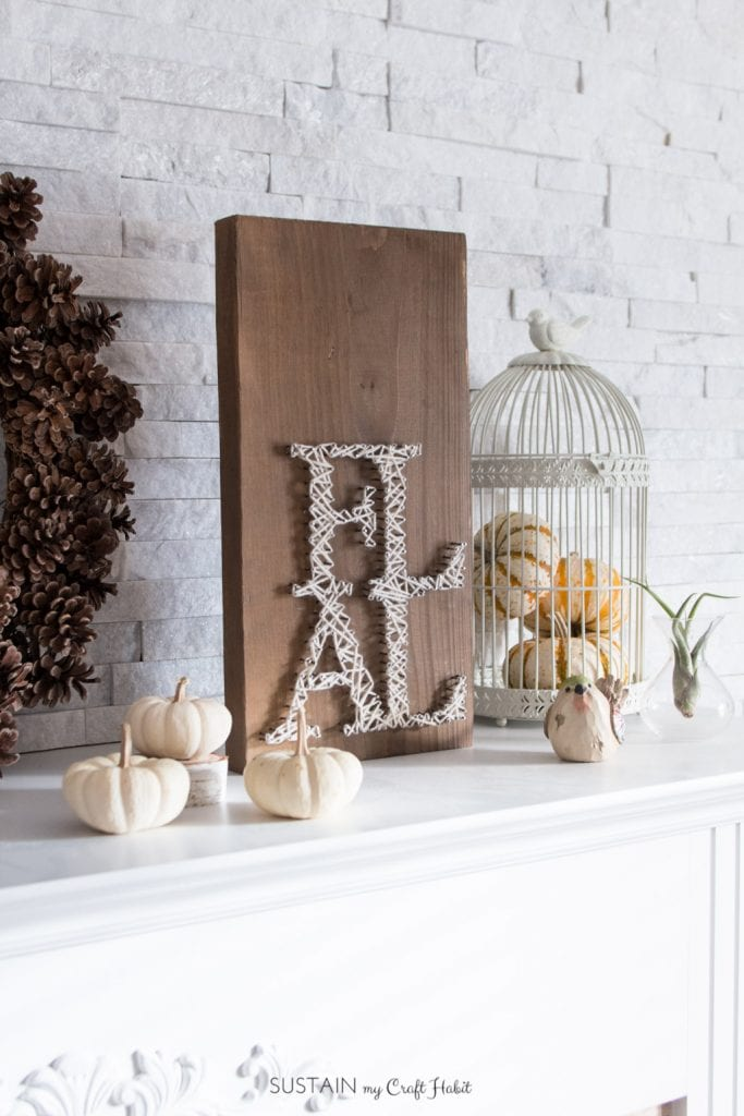 A fireplace mantle style with a farmhouse barn board fall string sign and neutral white pumpkin decor