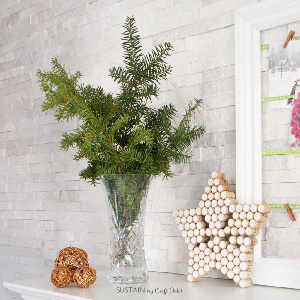 Rustic holiday mantel including foraged winter green branches and a sparkling star made from wine corks. #winecorkcrafts #winecorks #Christmasdecor