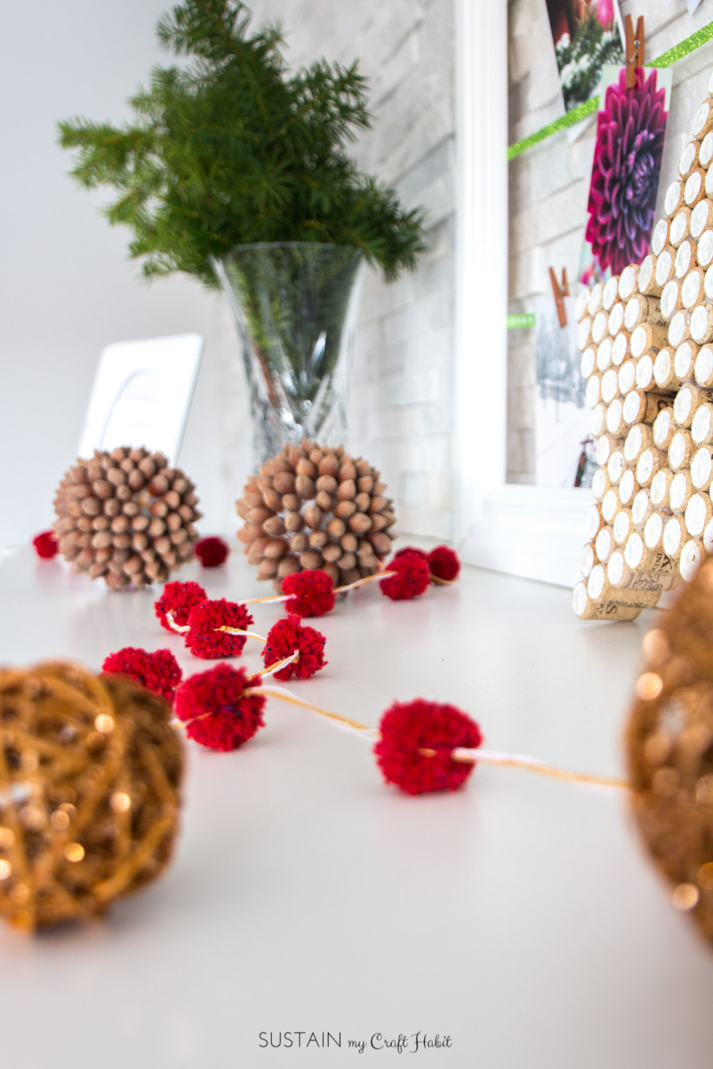 red diy pom pom garland on a fireplace mantel at christmas