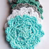 Teal, white and gray crochet coasters on a white surface