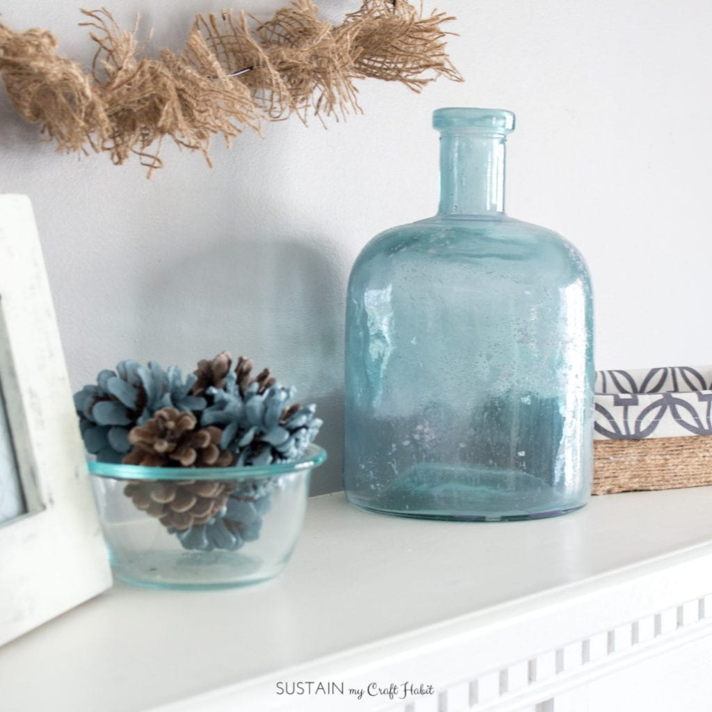 Frosted blue glass vase and natural elements in this spring rustic mantle.