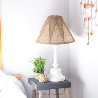Learn how to makeover an old brass lamp base and outdated shade simply using some spray paint and burlap ribbon.
