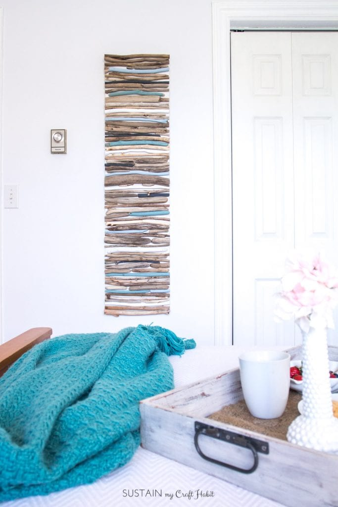 Create a beautiful coastal art piece for your wall using driftwood and a cool mix of blues, white and grey paint.