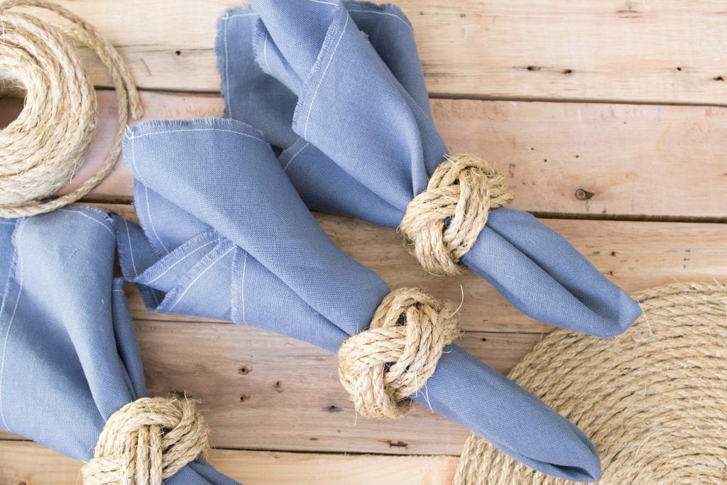 Three blue linen napkins on a rustic wood surface tied with DIY nautical knot napkin rings.