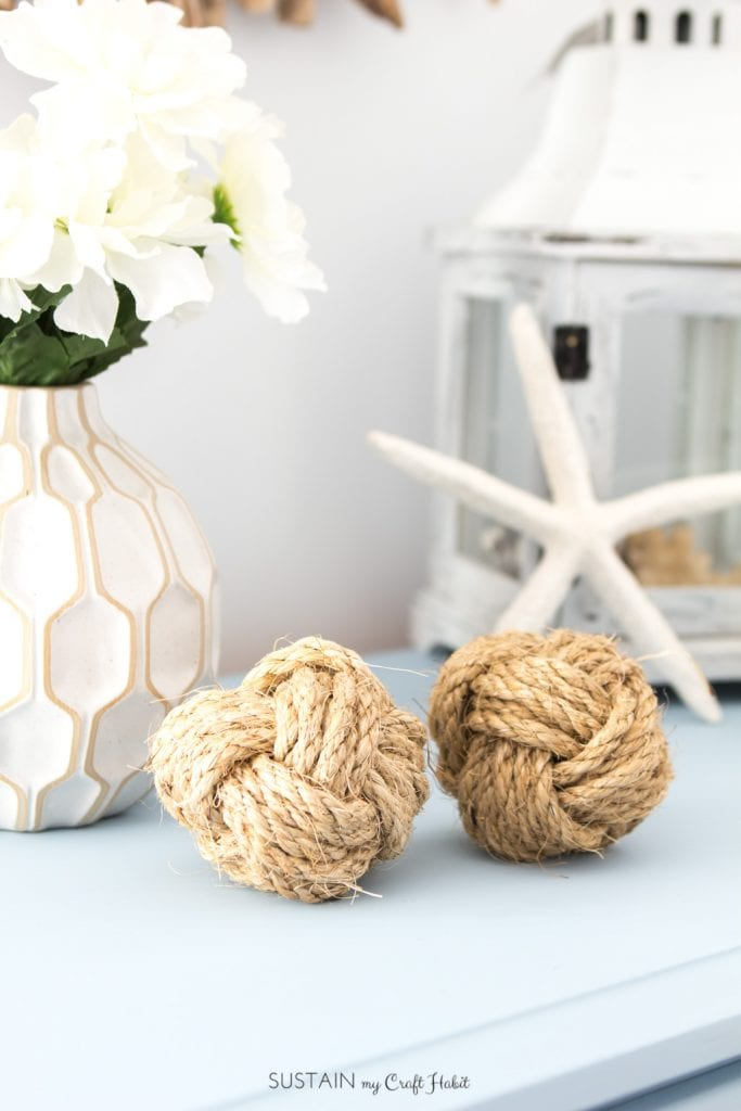 Two DIY monkey's fists nautical rope balls on a blue dresser with coastal home décor in the background