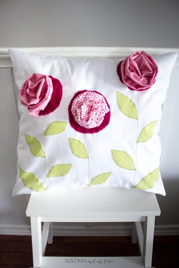 Throw pillow made with outgrown baby clothing. A DIY upcycling handmade gift idea.