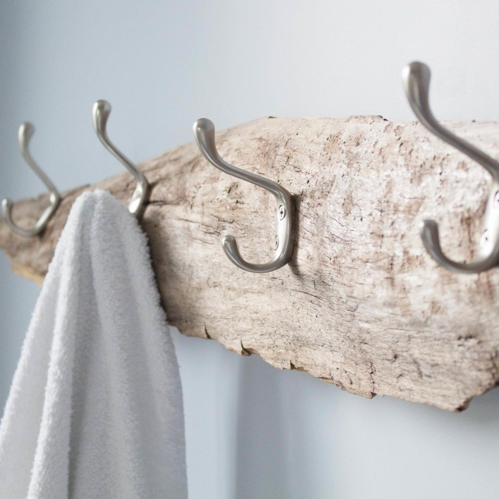 Make a handy towel rack with a piece of driftwood and some hardware store hooks.