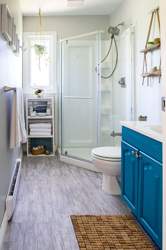 A coastal style bathroom with teal cabinet and grey floors as lake house decorating ideas