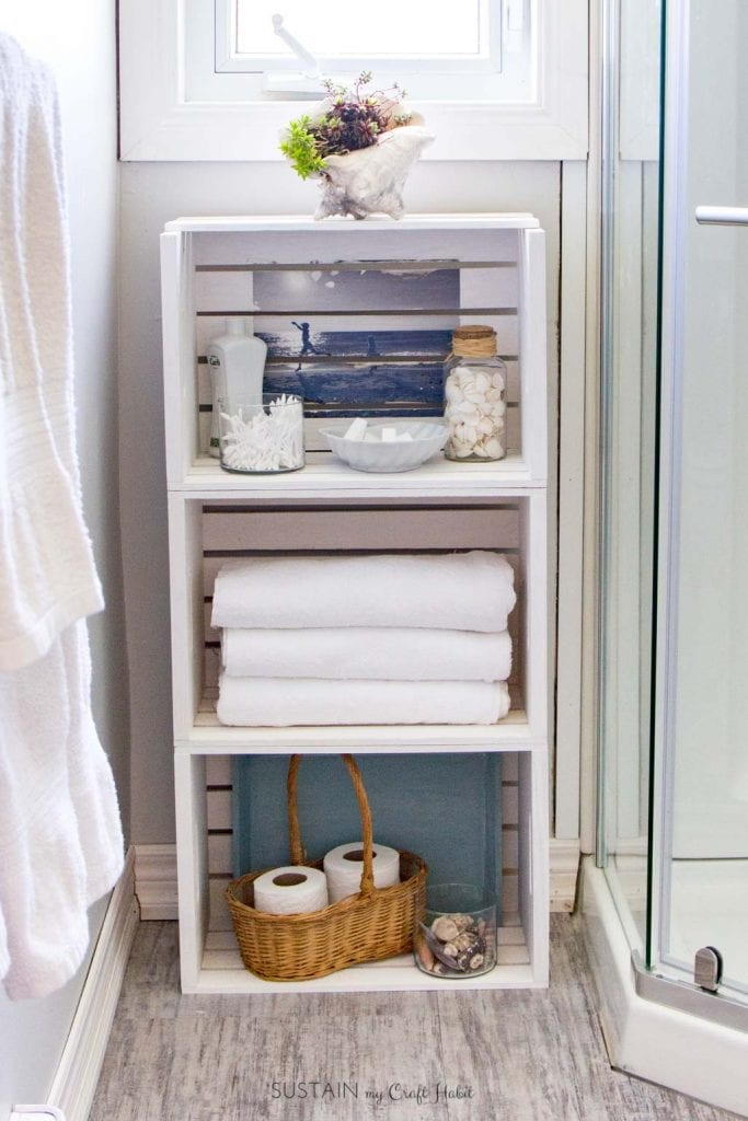 White washed stacked crate storage unit for a small, coastal style bathroom.