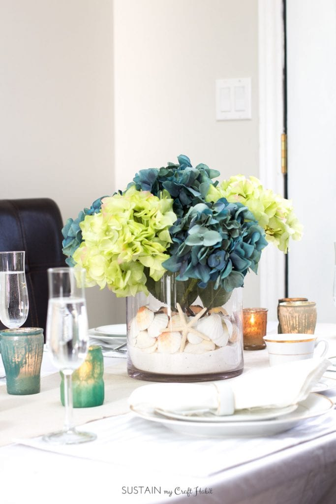 So beautiful! A summer tablescape including a DIY beach theme centerpiece with sea shells and hydrangeas from Afloral.com . Video tutorial included for this beach themed wedding, bridal shower or coastal cottage decorating idea! [sponsored]