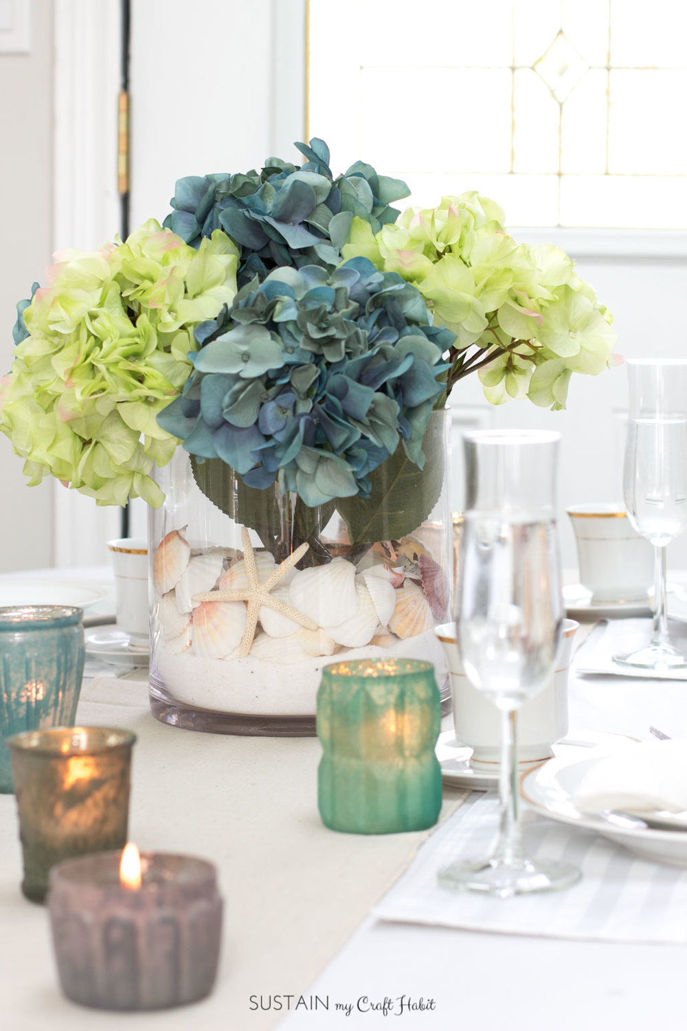 Learn how to make this simple beach theme centerpiece with sand, sea shells and hydrangeas. Video tutorial included!