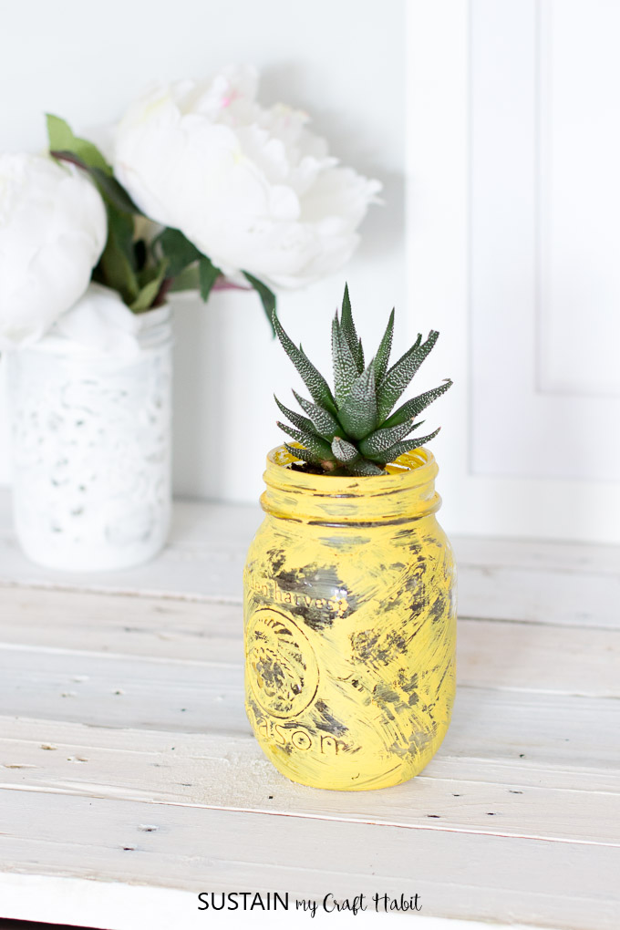 Upcycle a small mason jar into an adorable pineapple succulent planter. Hop on the pineapple trend with this simple DIY idea. Full tutorial with video included!