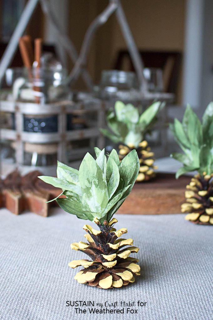 Adorable pineapple party idea! Make your own pineapple napkin weights with pine cones. Tips and tricks for cleaning pinecones for crafting.