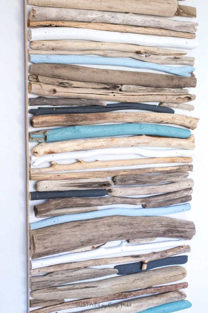 Wall art made with driftwood pieces painted in various shades of blue.