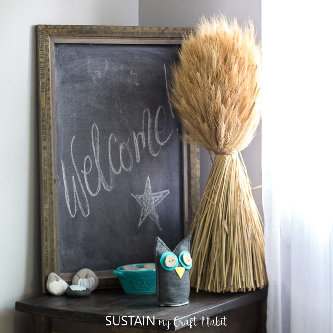 A corner of a room decorated for fall with wheat and a large farmhouse chalkboard