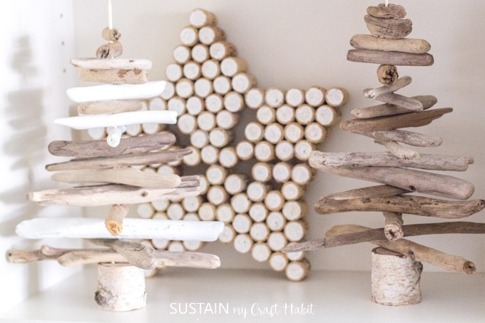 A star made from wine corks behind two small driftwood trees on a white bookshelf