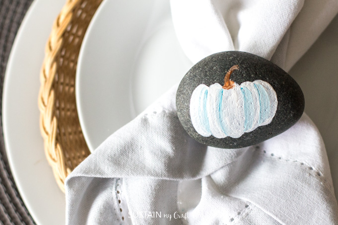 These painted pumpkin rocks make adorable Thanksgiving decor. Learn how to paint your own with this video tutorial plus other rock painting ideas. #paintedrocks #rockpaintingideas #diy #thanksgivingcrafts