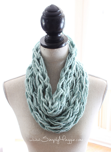 Finger knitted scarf in light blue, hanging around a mannequin's neck.
