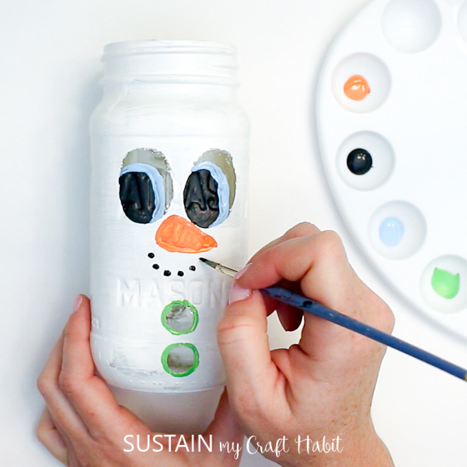 Painting a carrot nose onto the Ball jar snowman craft