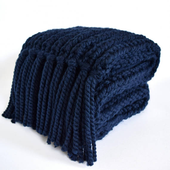 Folded navy blue knitted scarf with tassels.