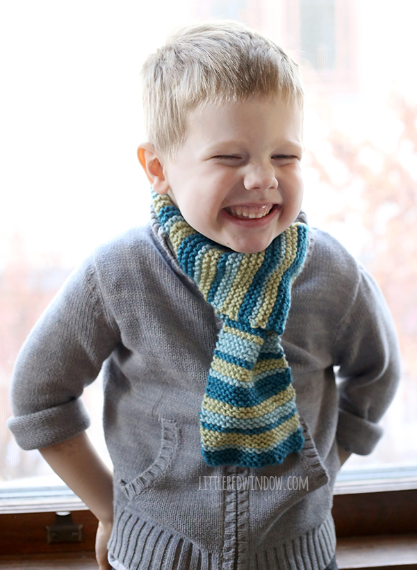 Child smiling and wearing a striped knitted scarf.