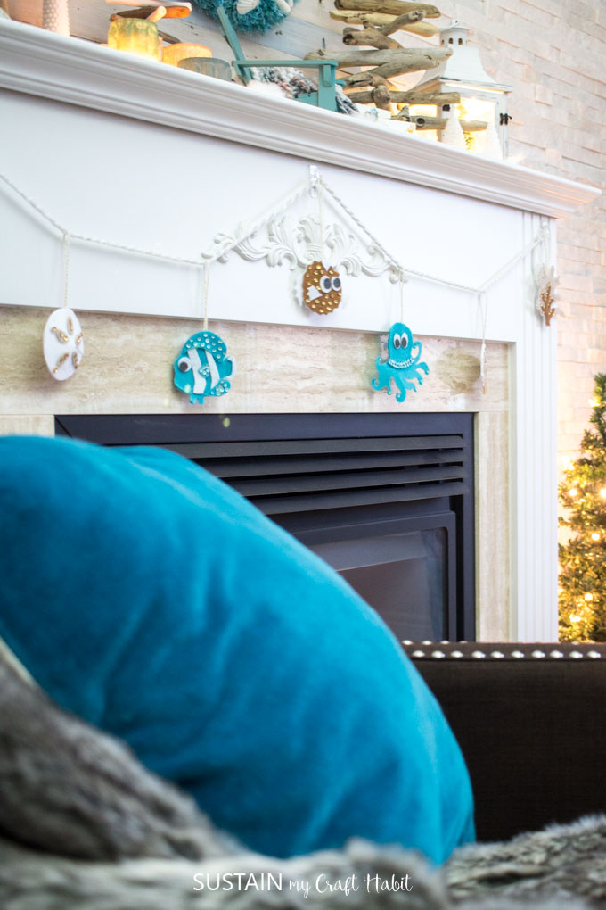 Garland of felt no-sew beach themed ornaments hung on a fireplace mantle with a teal throw pillow in the foreground