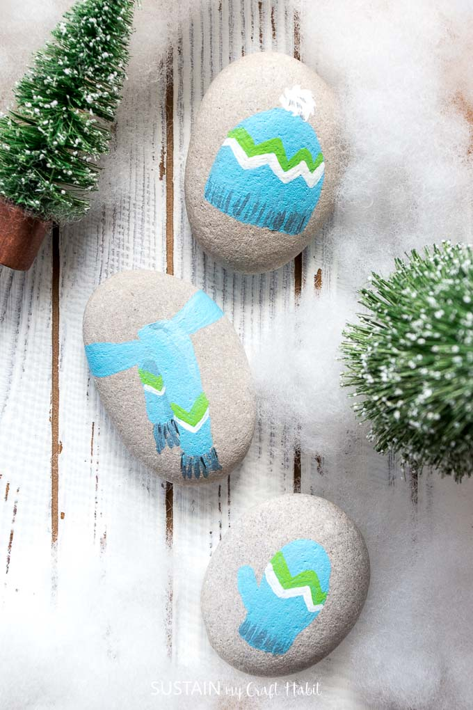 Over a dozen Christmas Rock Painting Ideas! Rock painting Christmas holidays | Canadian bloggers craft hop | #christmascrafts #rockpainting #rusticchristmas | step-by-step DIY rock painting tutorial for beginners | Festive painted beach stones | Hat, scarf, mitten
