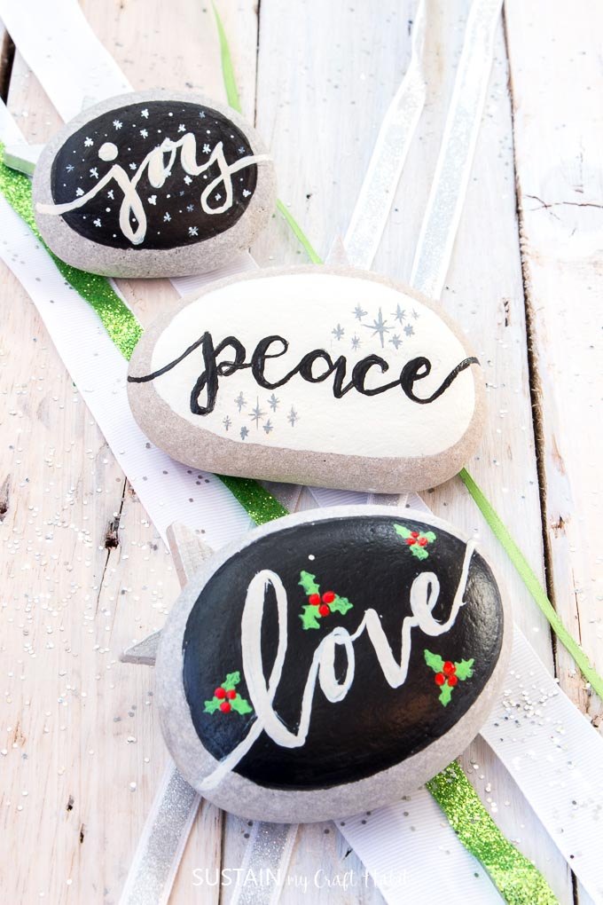 Over a dozen Christmas Rock Painting Ideas including Love, Peace, Joy! Rock painting Christmas holidays | Canadian bloggers craft hop | #christmascrafts #rockpainting #rusticchristmas | step-by-step DIY rock painting tutorial for beginners | Festive painted beach stones