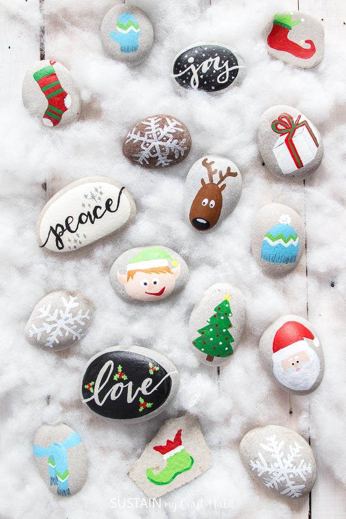 A collection of Christmas themed painted rocks including a reindeer, Santa, tree, snowflakes and more on a white wood surface.