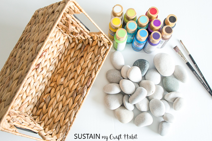 Top view of round beach stones and a variety of acrylic craft paints beside a basket on a white surface