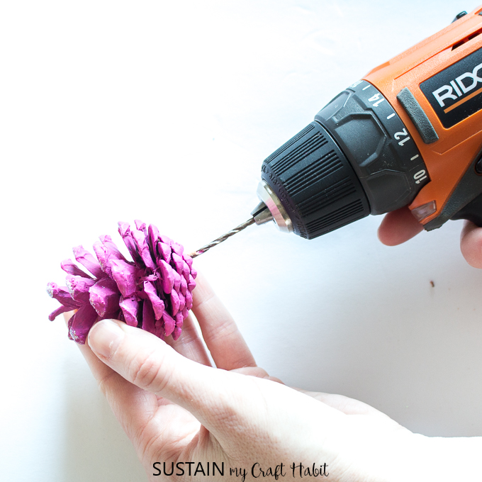 Drilling a hole at the bottom of a painted pine cone.