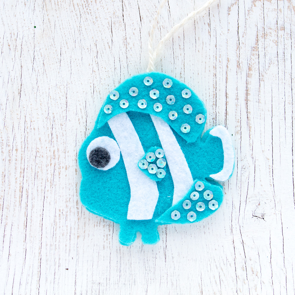 Teal and white clown fish felt ornament on a weathered wood background