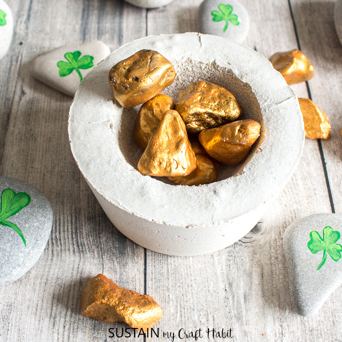 A small cement pot filled with gold painted rocks surrounded by rocks with shamrocks painted onto them.