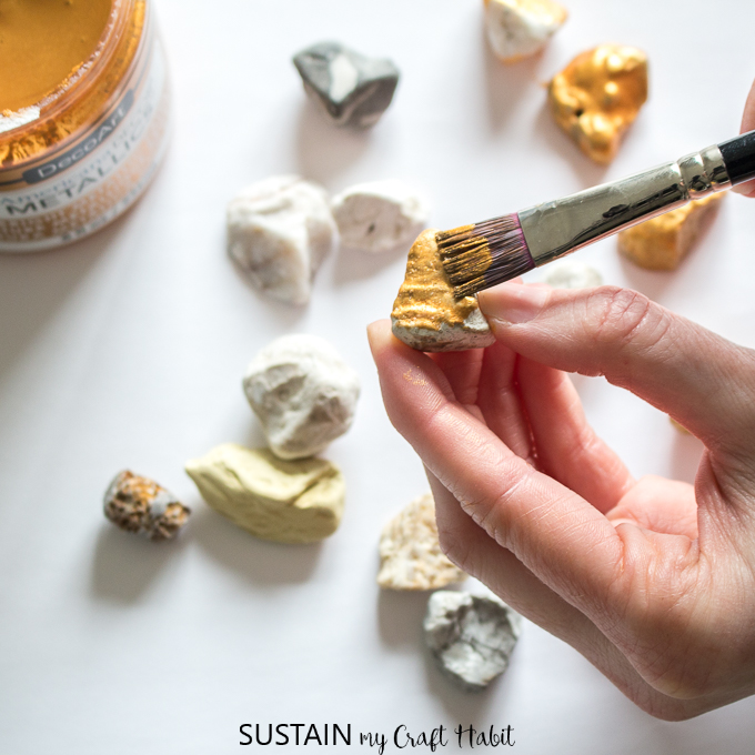 Painting a rock with gold paint.