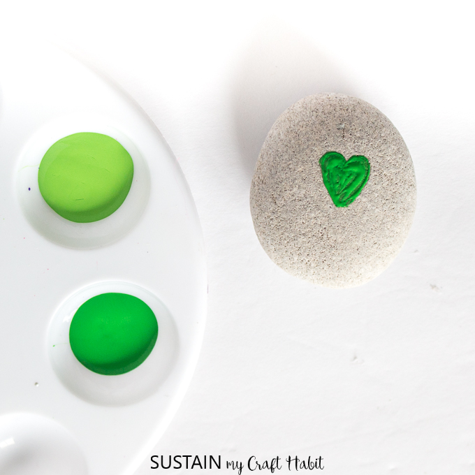 One small green heart painted onto a round gray rock as the start of the shamrock St. Patrick's Day craft idea.