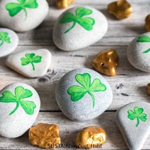 Beach stones painted as gold nuggets and shamrocks as examples of st. patrick's day crafts