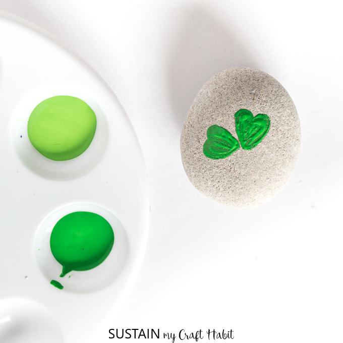 Two small green hearts painted on to the beach rock.