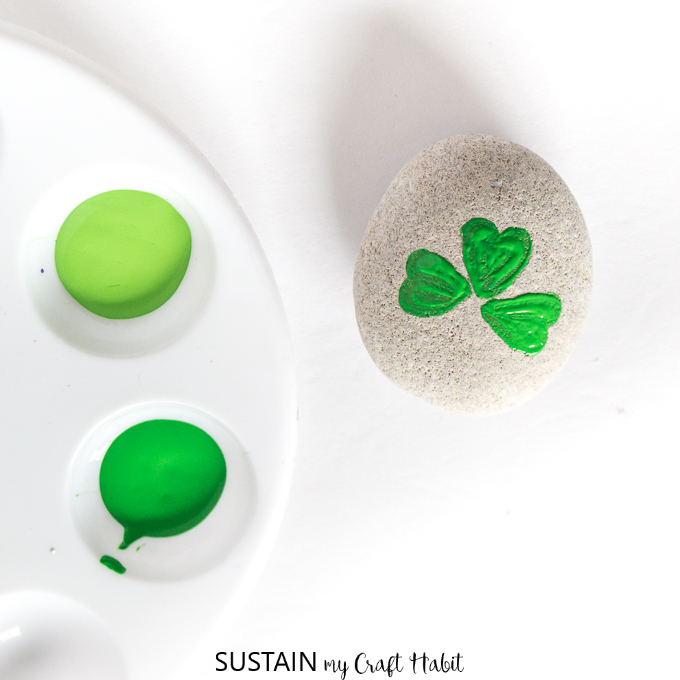 Painting three small hearts as the petals of the shamrock.