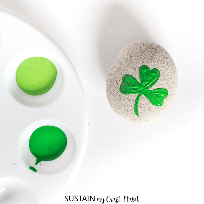 Painting the first layer of the shamrock on a round grey beach stone.