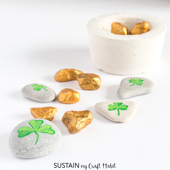 Several gold painted rocks and stones with painted shamrocks on a white surface.