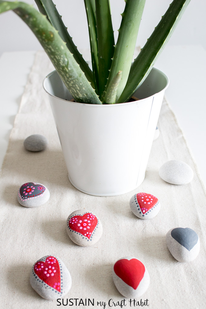 set of painted heart rocks on a burlap table runner