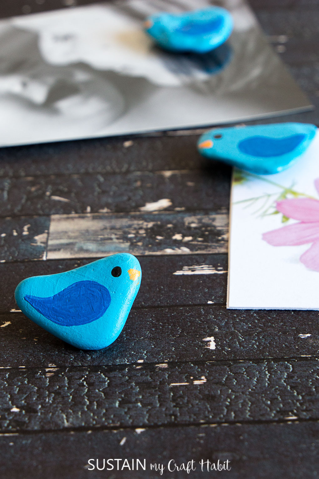 Small rocks painted to look like teal and blue birds placed on a dark wood background