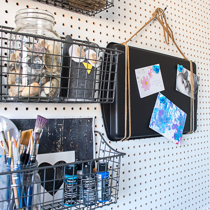 A white pegboard filled with crafting supplies including easy painted rocks crafts
