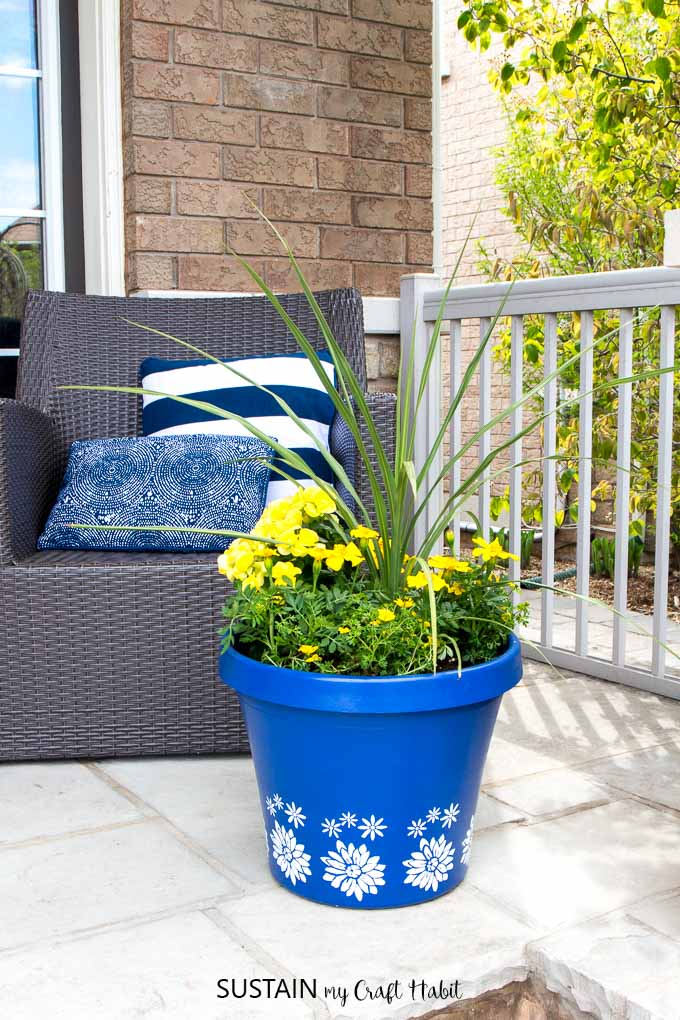 A blue flower pot filled with yellow spring flowers on a front porch