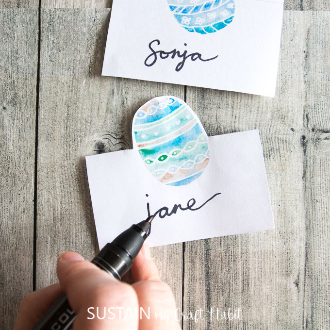 Hand lettering an Easter place card on a rustic wood background