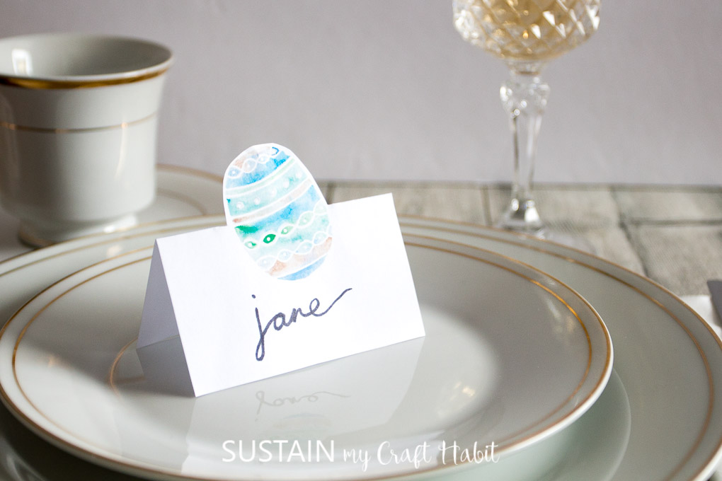 Beautiful Easter tablescape with gold rimmed plates and a printable Easter egg place card