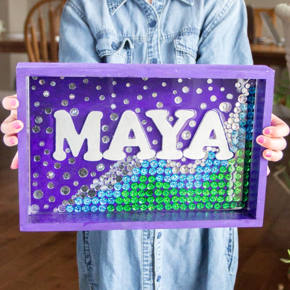 Child holding a personalized mermaid wall art sign in purple, green, blue and silver