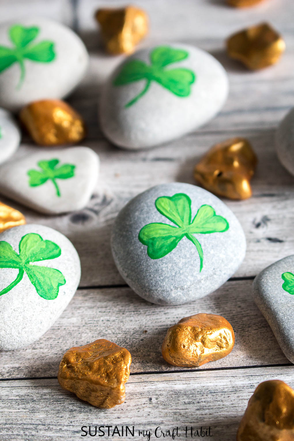 Completed shamrock and gold nugget painted rocks on a grey wood surface as an example of St Patrick's Day crafts ideas.