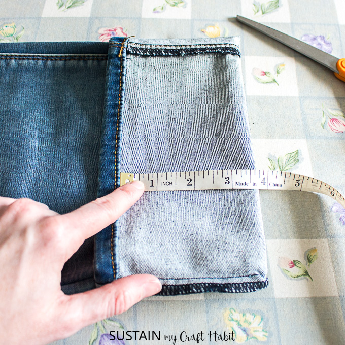 measuring the new hem for hemming jeans with the original hem