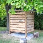 DIY outdoor shower enclosure built of wood slats under a catalpa tree
